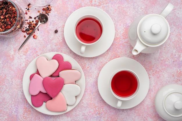 De koekjes van de hartvorm met suikerglazuur met bessenthee. concept: valentijnsdag theekransje, feestelijke tafel instelling in roze. Premium Foto