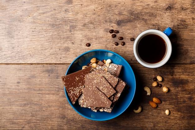 De koffie en de noten van het chocoladesuikergoed op hout Gratis Foto