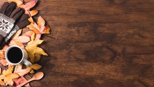 De koffiekop en de handschoenen op de herfstbladeren kopiëren ruimte Gratis Foto