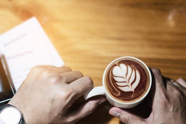De koffiekop en instapkaart die van de mensenholding op vluchtreis wachten door vliegtuig Gratis Foto