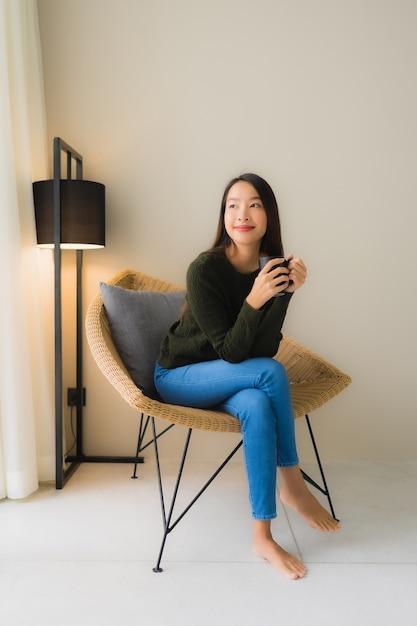De koffiekop van de portret mooie jonge aziatische vrouwengreep en het zitten op bankstoel Gratis Foto
