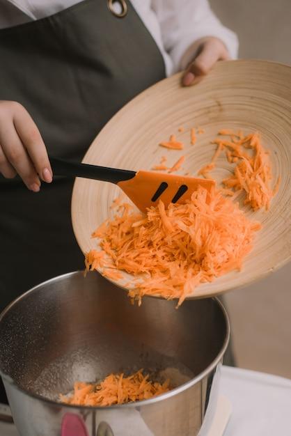 De kok voegt de geraspte wortelen toe aan de metalen kom. de vrouwelijke hand zette gehakte wortel in houten kom met salade in keuken. groenten koken Premium Foto
