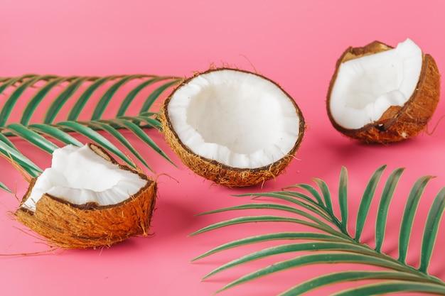 De kokosnotenhelften op een helder roze Premium Foto