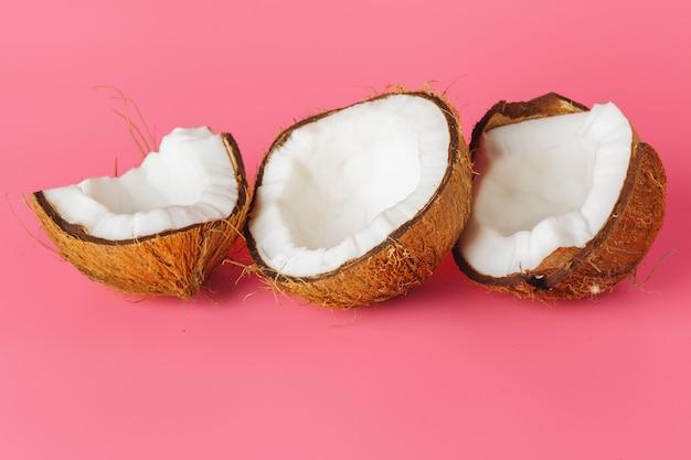 De kokosnotenhelften op een heldere roze achtergrond Premium Foto