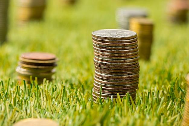 De kolommen van munten op gras Gratis Foto