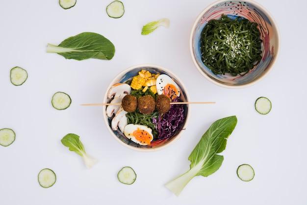 De kom van zeewiersalade met ramen traditioneel aziatisch die voedsel met komkommerplakken en blad op witte achtergrond wordt verfraaid Gratis Foto