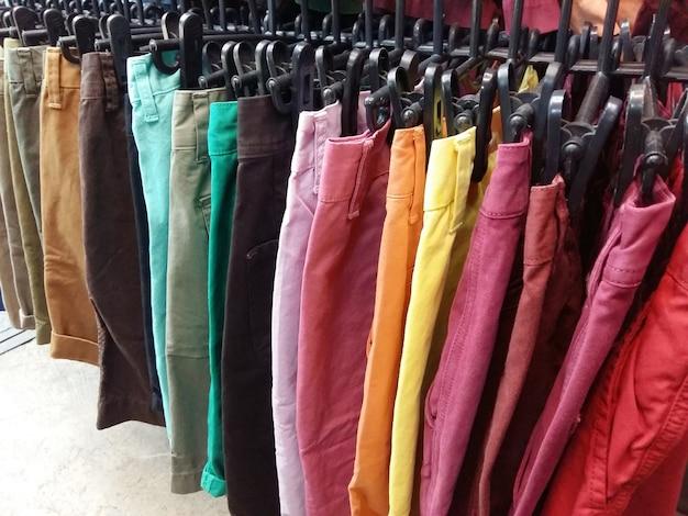 De korte broek van de kleurrijke man en van de vrouw op hangers Premium Foto