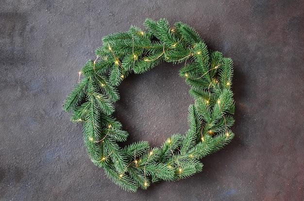 De kroon van de kerstdeur gemaakt van boom fir takken met lichten Premium Foto