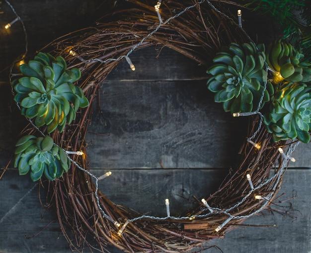 De kroon van de kerstdeur gemaakt van takken en suculentus. Gratis Foto