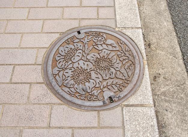 De kunst boven de afvoerkap op straat in fukuoka prefecture Premium Foto
