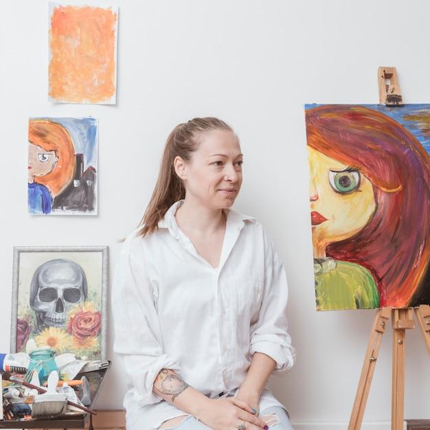De kunstenaarszitting van de vrouw in workshop Gratis Foto