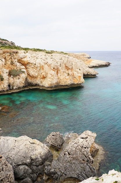 De kustlijn met rotsachtige bergen en kalm water onder de blauwe lucht Gratis Foto