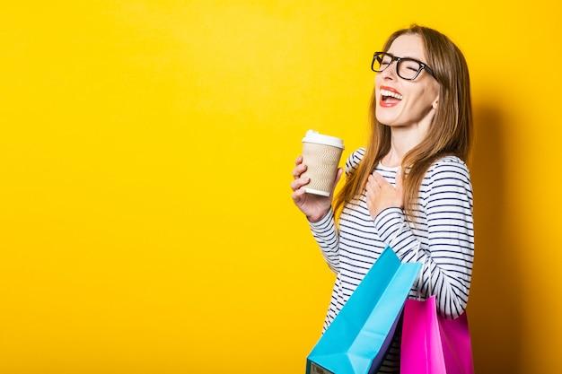 De lachende jonge vrouw verheugt zich met een papieren beker met koffie en tassen op een gele achtergrond Premium Foto