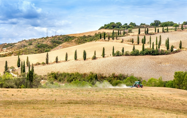 De landbouw ploegende tractor met een landbouwer ploegt het gebied na de oogst Premium Foto