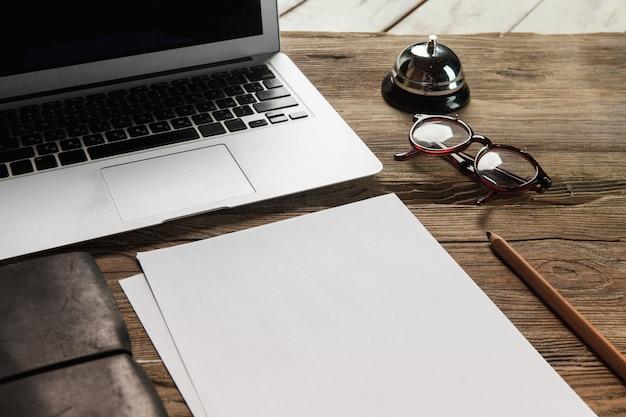 De laptop, blanco papier, glazen en kleine bel op de houten tafel Gratis Foto