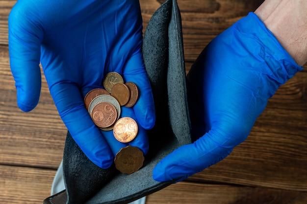 De lege blauwe portefeuille dient binnen medische handschoenen met muntstukken na financiële economische crisis in Premium Foto