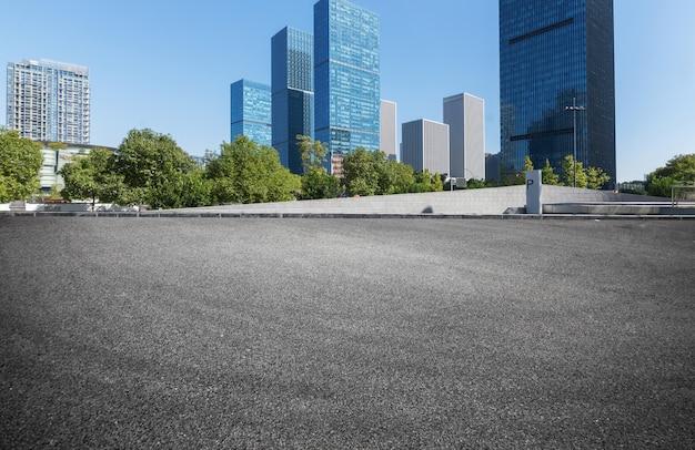De lege oppervlakte van de wegvloer met de moderne gebouwen van het stadsoriëntatiepunt in china Premium Foto
