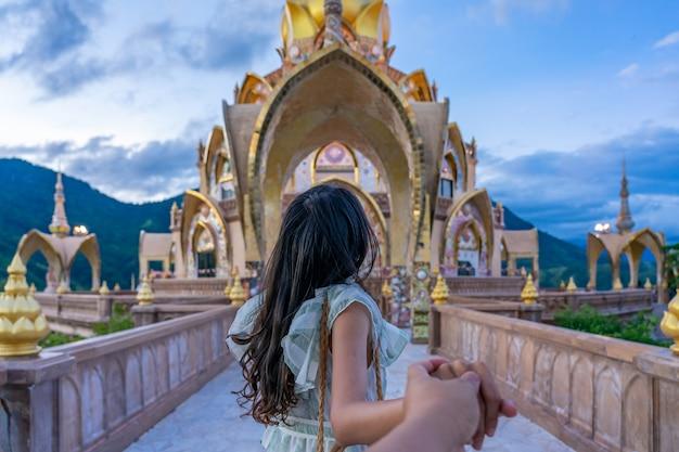 De leidende vriend van de jonge vrouwenreiziger tot de mening van hoofdpagode in wat phra that pha son kaew-tempel in phetchabun, thailand. Premium Foto