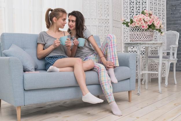 De lesbische kop van de paarholding van koffiezitting op bank die elkaar bekijken Gratis Foto