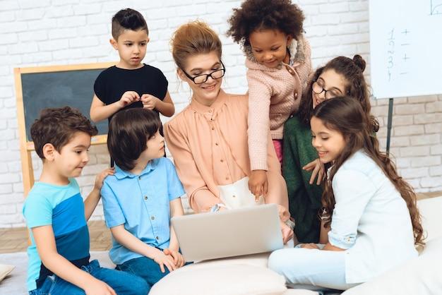 De leuke leraar zit met schoolkinderen bekijkt laptop Premium Foto