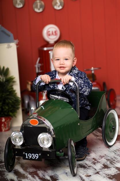 De leuke peuter speelt met speelgoedauto's, berijdt een stuk speelgoed schrijfmachinevliegtuig, gelukkige kinderjaren Premium Foto