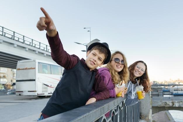 De levensstijl van adolescenten, jongens en twee tienermeisjes loopt in de stad Premium Foto