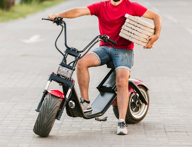 De leveringskerel van de close-up op motorfiets met pizza Gratis Foto