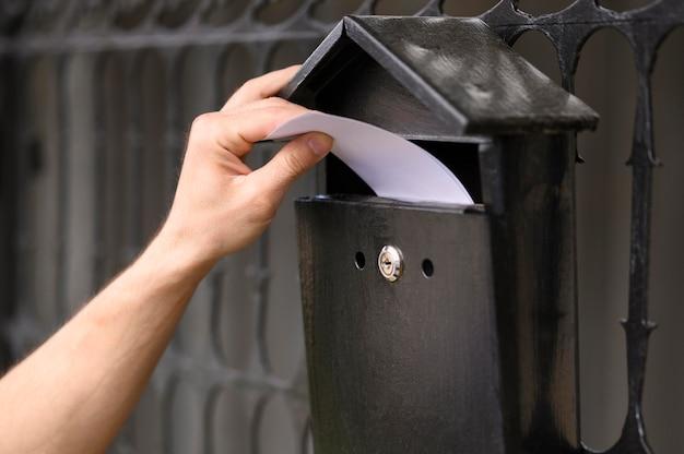 De leveringsmens die van de close-up envelop in de brievenbus laat vallen Gratis Foto