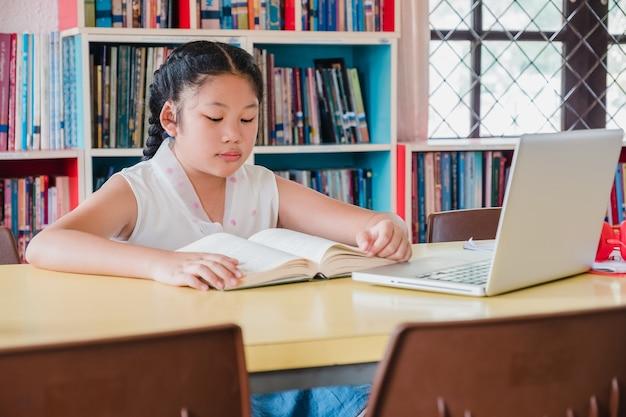 De lezingsboek van de tiener met laptop computer in bibliotheek. onderwijs en geletterdheidsconcept Premium Foto