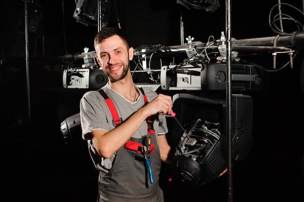 De lichttechnicus repareert het lichtapparaat op het podium Premium Foto