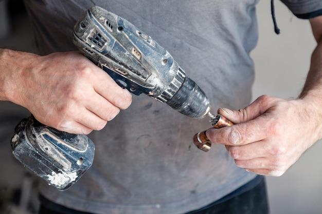 De loodgieter hoofd schoonmakende koperpijpen van de close-uparbeider met professionele borstel. Premium Foto
