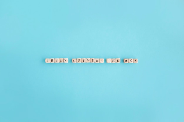 De luchtmening van denkt buiten de doostekst gemaakt met kleine blokken op blauwe achtergrond Gratis Foto