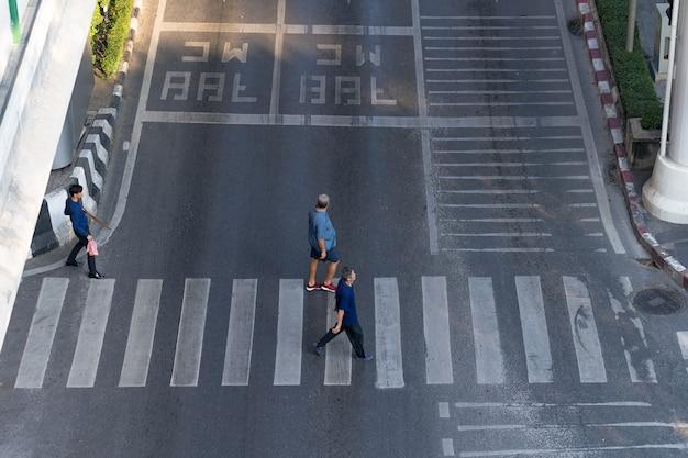 De luchtmeningsfoto van mensen loopt op straat in de stad over voetgangersoversteekplaatsverkeersweg Premium Foto