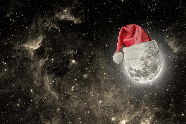 De maan draagt een hoed voor kerstmis Premium Foto