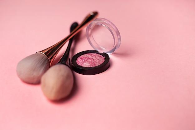 De make-upborstel en bloost op een roze achtergrond. schoonheid concept. close-up met ruimte voor tekst Premium Foto