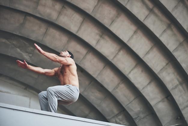 De man beoefent buitenshuis parkour, extreme acrobatiek. Gratis Foto