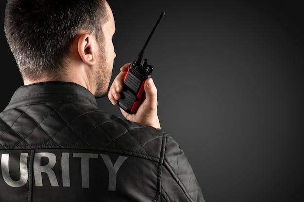 De man, beveiliging, houdt een walkietalkie vast Premium Foto