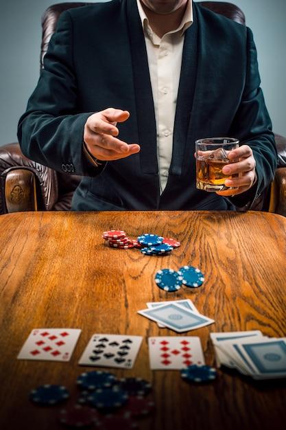 De man, chips voor gokken, drinken en kaarten spelen Gratis Foto