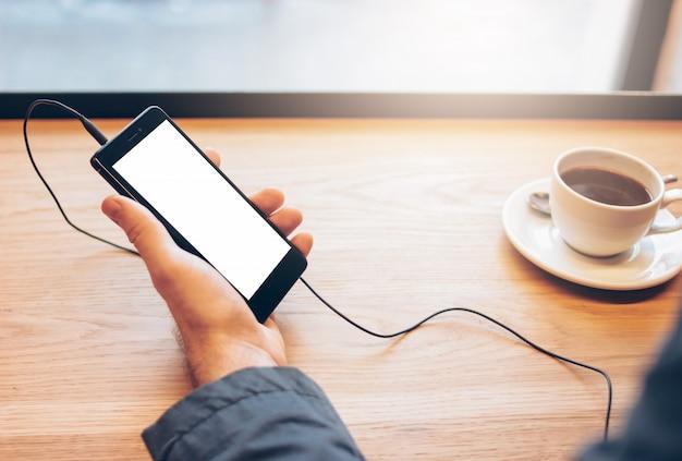 De man die mobiele telefoon met hoofdtelefoons met behulp van in koffie Premium Foto