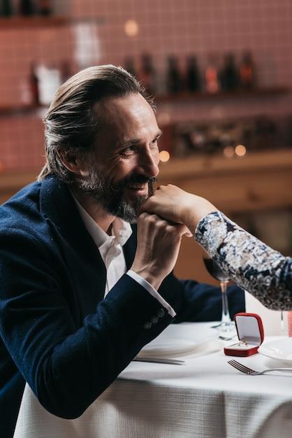 De man doet een huwelijksaanzoek en gaat de hand van een vrouw kussen in een restaurant Premium Foto