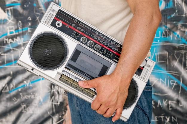 De man draagt een vintage boombox naast een muur met graffiti Premium Foto