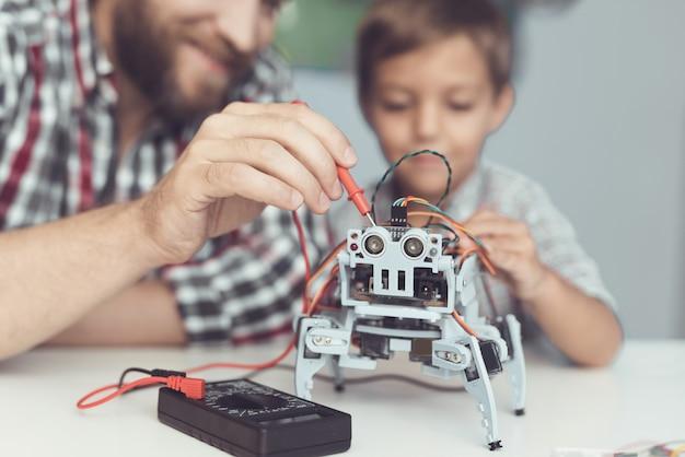 De man en de kleine jongen meten de prestaties van de robot. Premium Foto