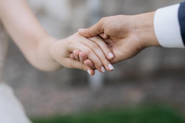 De man en de vrouw houden elkaar in openlucht samen handen Gratis Foto