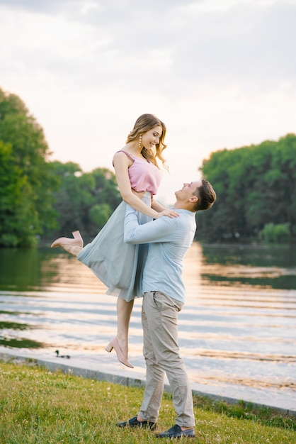 De man hief zijn handen op rond de taille van zijn vriendin en keek haar aan, ze glimlachen en gelukkig Premium Foto