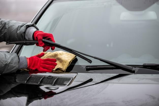 De man houdt de microfiber in de hand en polijst de voorruitclose-up. Premium Foto