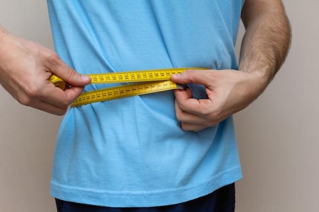 De man in een blauw t-shirt meet de taille met gele tape Premium Foto