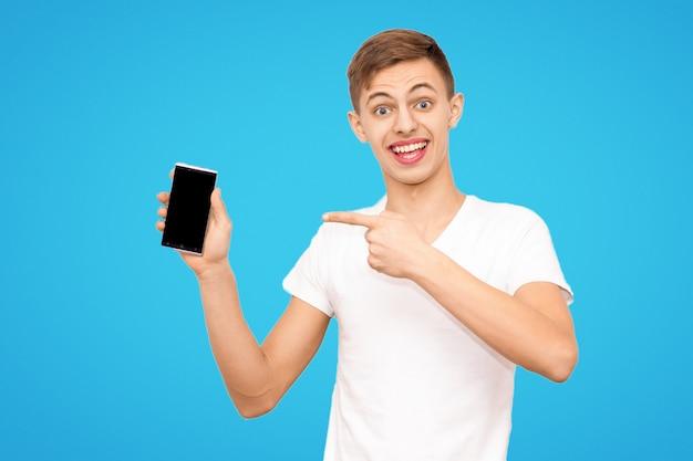 De man in het witte t-shirt adverteert de telefoon geïsoleerd op een blauwe achtergrond Premium Foto