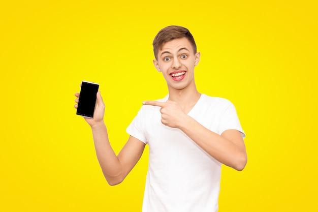 De man in het witte t-shirt adverteert de telefoon geïsoleerd op een gele achtergrond Premium Foto