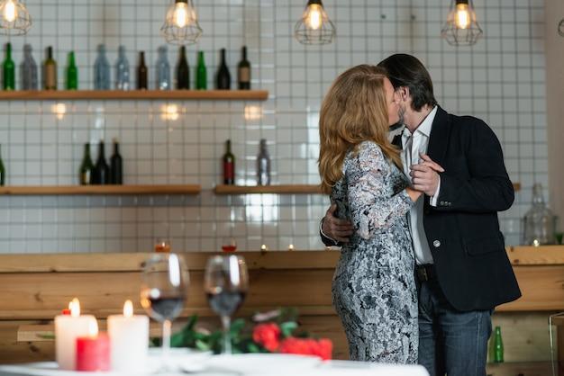 De man knuffelt de vrouw bij de taille die in de restaurantzaal staat Premium Foto