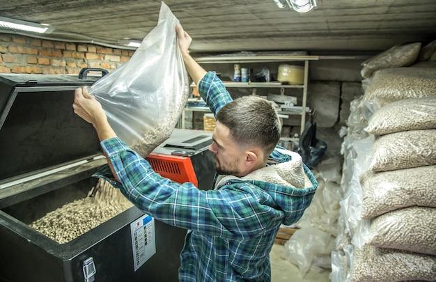 De man laadt de pellets in de vaste brandstofketel, werkt met biobrandstoffen, zuinig stoken Gratis Foto